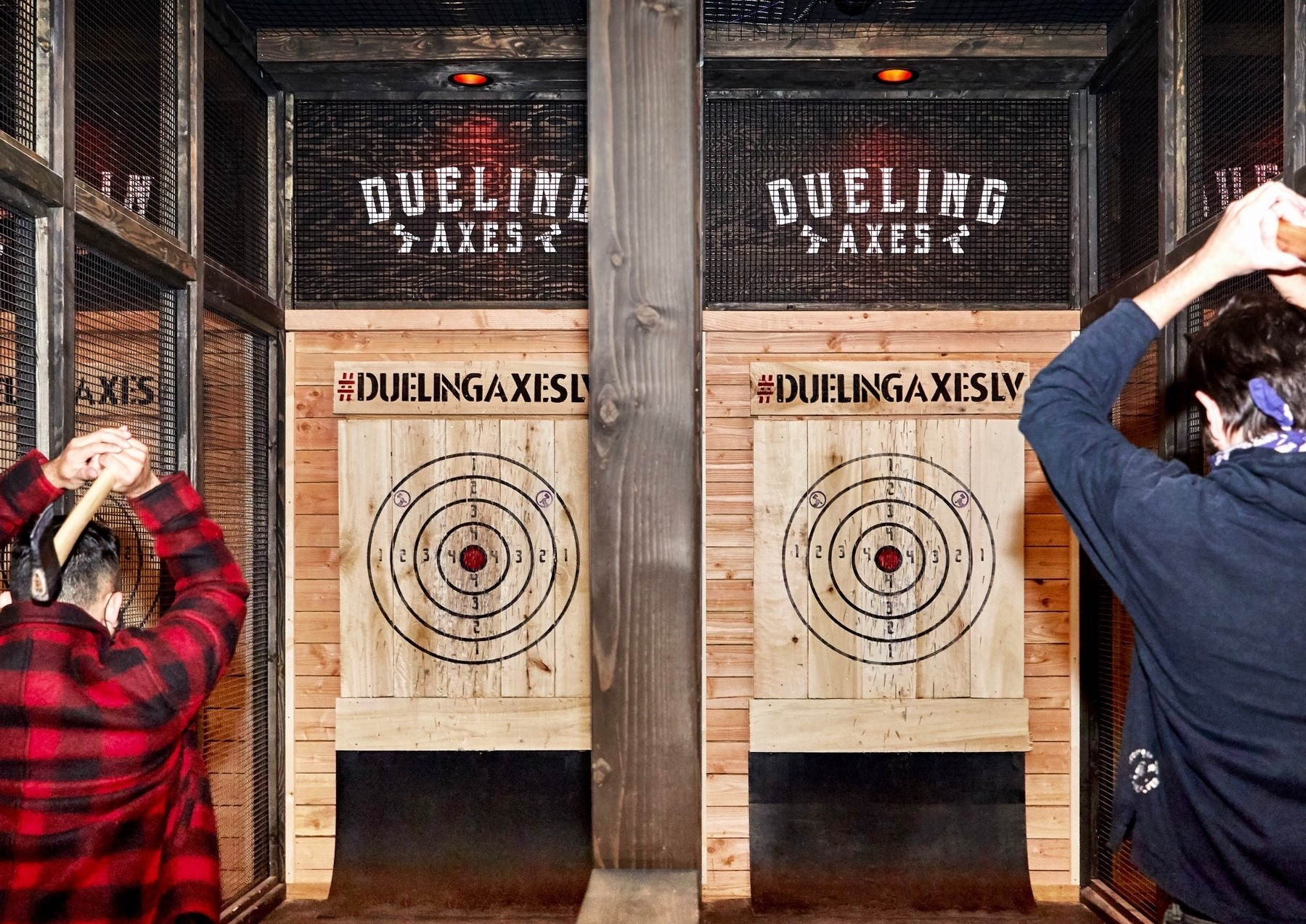 Two people throwing axes at Dueling Axes Las Vegas inside Area15
