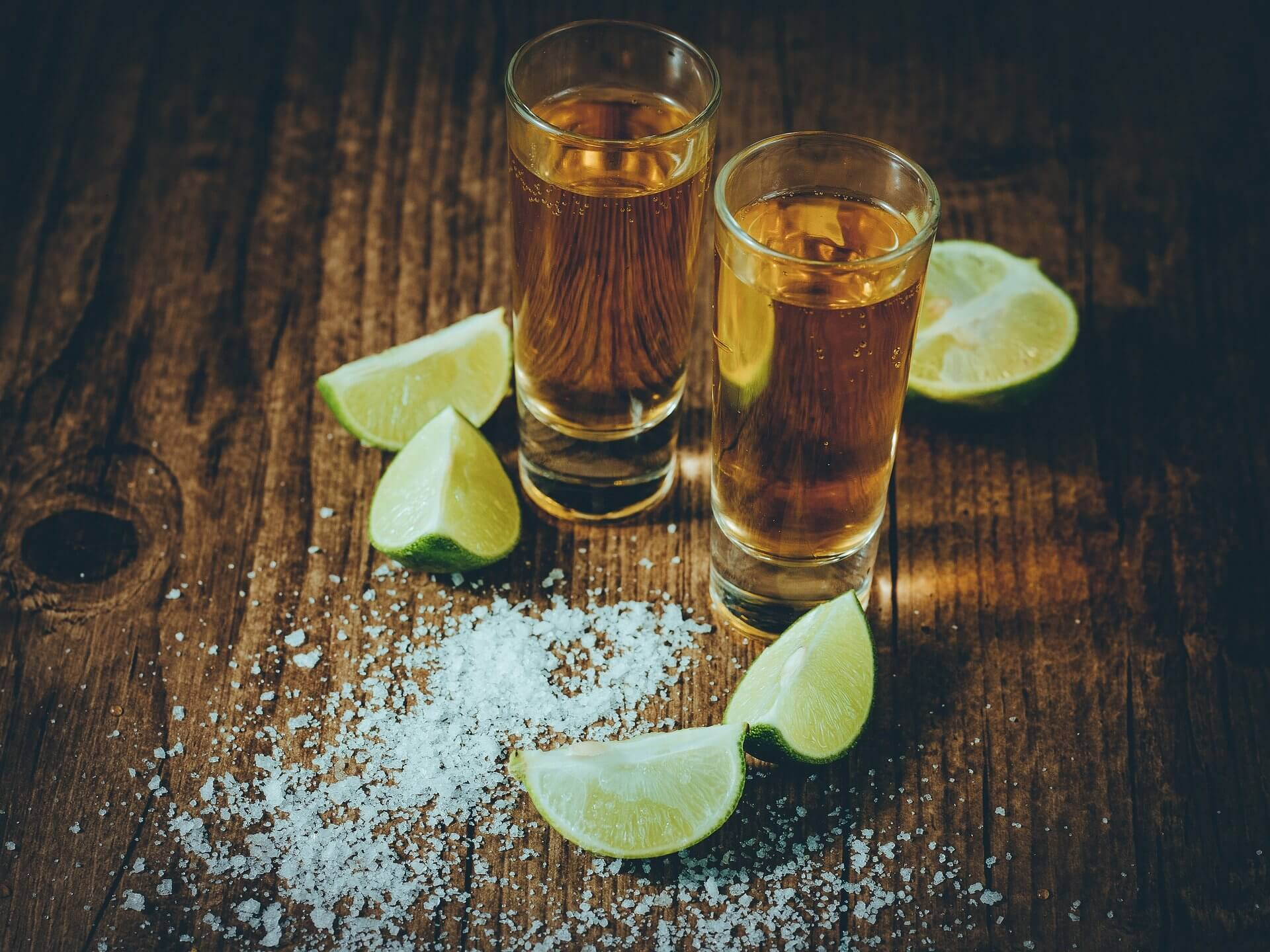 Shots of tequila surrounded by lime wedges and salt