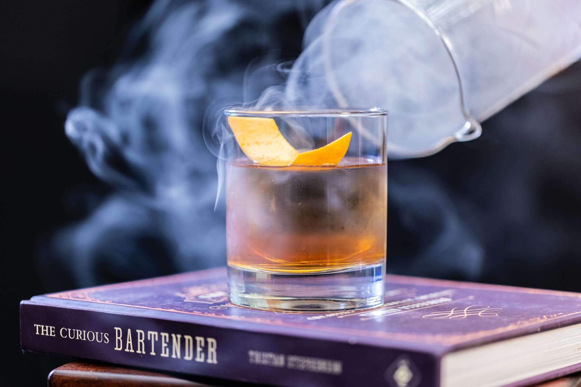 Cocktail and smoke on top stack of books